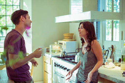 Couple discussing finances in kitchen